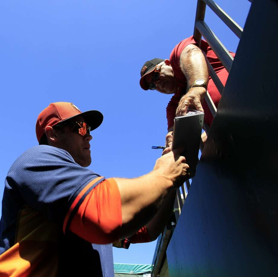 Preston Tucker signs autographs for fans from the dugout. Photo: Karen Warren, Houston Chronicle
