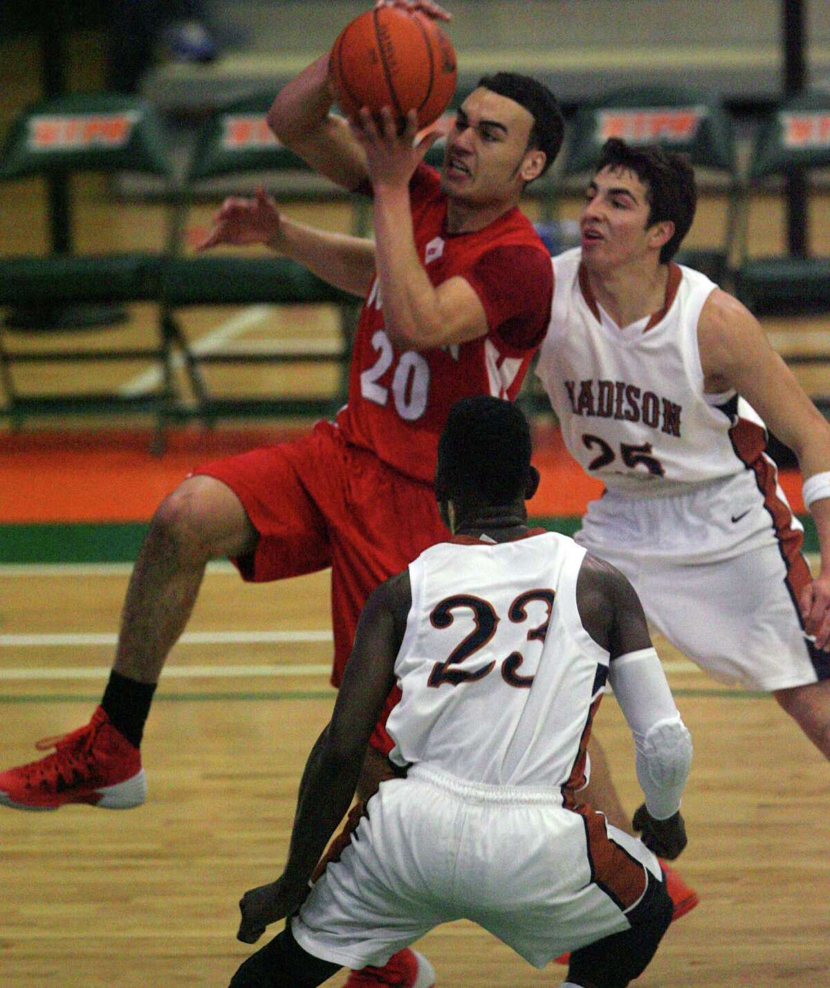 Judson's Tony Allen drives to the basket Saturday against Madison's Ja'Michael Brown and Troy Guajardo in regional play.