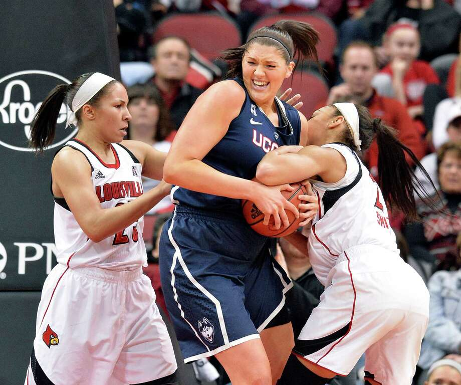 Connecticut's Stefanie Dolson, center, battles Louisville's Tia Gibbs, Left, and Bria Smith for a rebound during the first half of an NCAA college basketball game Monday, March 3, 2014, in Louisville, Ky. Photo: Timothy D. Easley, AP / Associated Press