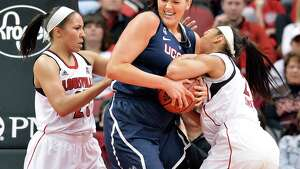 Connecticut's Stefanie Dolson, center, battles Louisville's Tia Gibbs, Left, and Bria Smith for a rebound during the first half of an NCAA college basketball game Monday, March 3, 2014, in Louisville, Ky.
