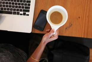 Priya Wadhera reaches for her coffee while working on her laptop at Coffee Bar on August 8, 2013 in San Francisco, Calif. Coffee Bar reserves 8-10 tables (not pictured) between 11:30 and 2:30 that don't allow computers and have a 30 minute time limit. The restaurant has seen a 15 to 20 percent increase in business as a result of this practice.