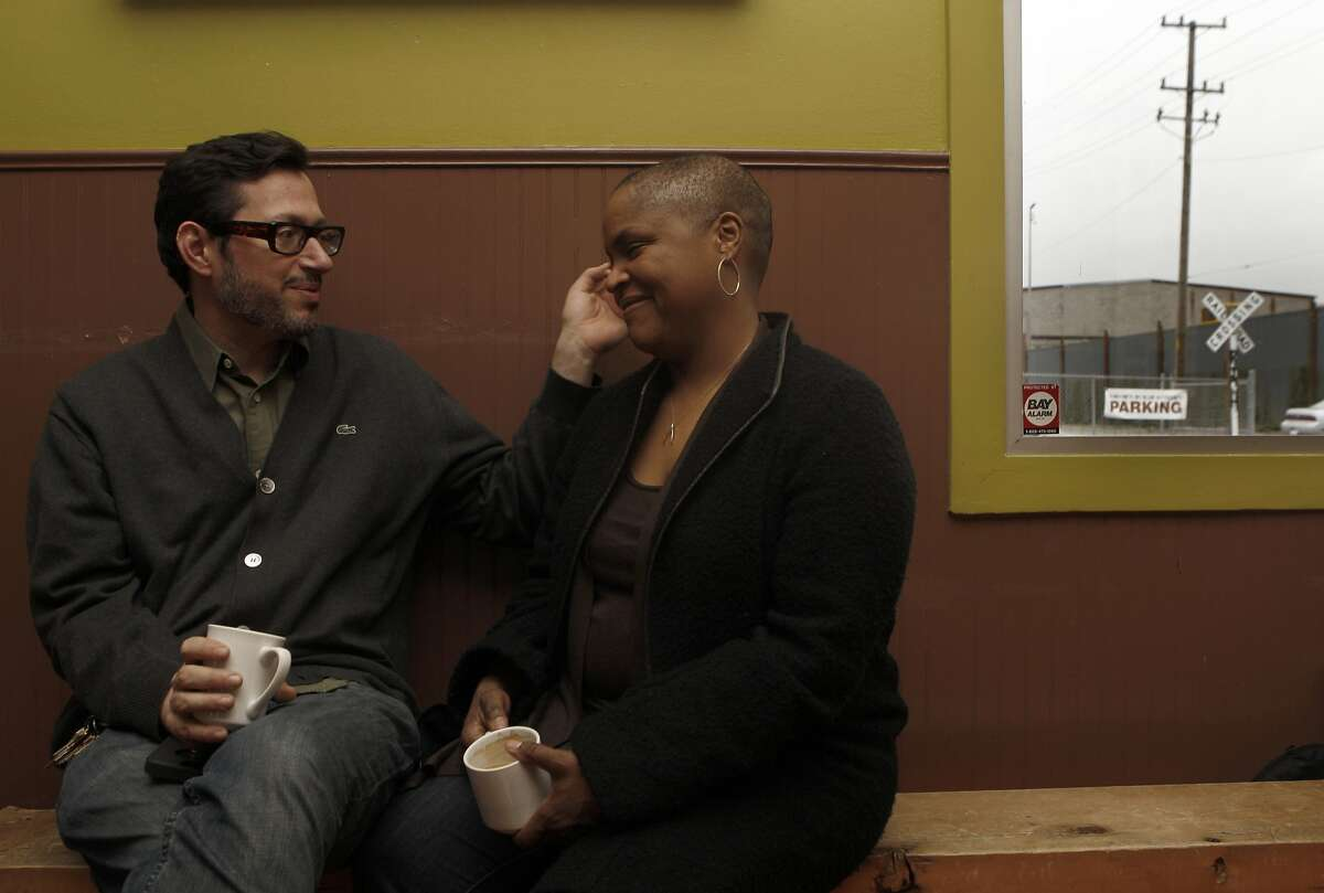 Husband Phil Surkis (left) shares a warm moment with chef Tanya Holland (middle) as they have morning coffee at Brown Sugar Kitchen in Oakland, Calif., on Wednesday, February 29, 2014.