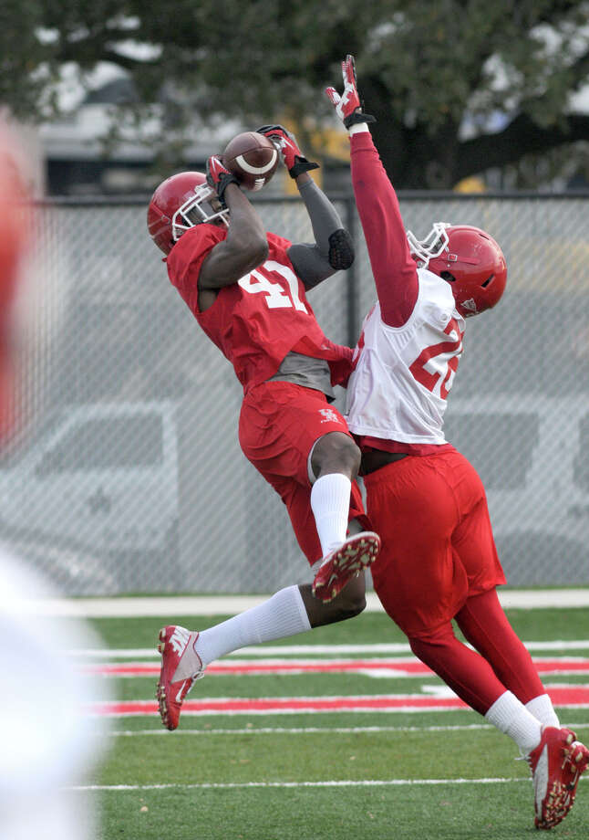 UH junior wide receiver Kelechi Ejekam, left, makes a catch against sophomore defensive back Brandon Wilson during the Cougars' first spring football practice. Photo: Jerry Baker, For The Chronicle