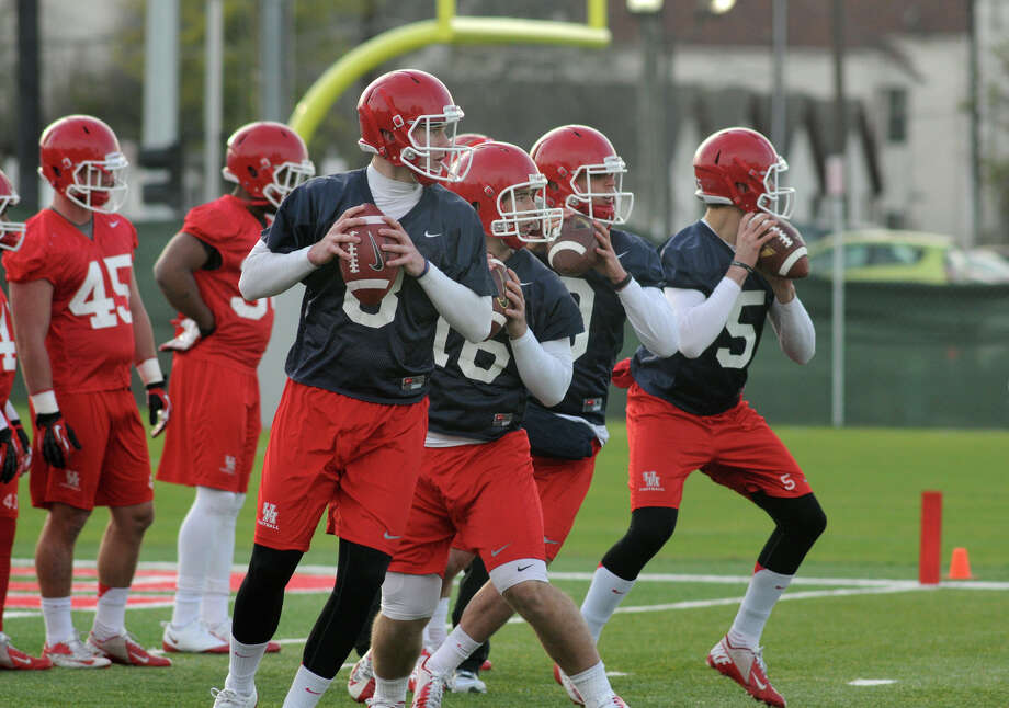 UH quarterbacks Hunter McCoy, Bear Fenimore, Billy Cosh and John O'Korn work in unison during the Cougars' first spring football practice. Photo: Jerry Baker, For The Chronicle