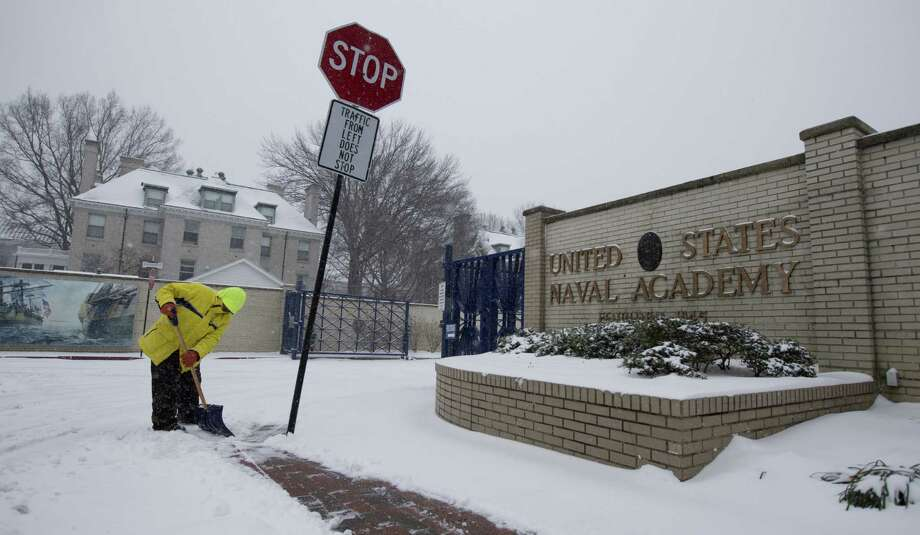 """Carlo Flore shovels snow on a sidewalk in front of the U.S. Naval Academy in Annapolis, Md., as snow accumulates in the area. Spring is hardly in sight. """"It's one of the more disruptive winters of the last several decades,"""" says one climatologist. Photo: Carolyn Kaster / Associated Press / AP"""