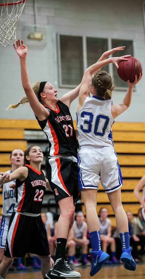 Ridgefield high school's Rebecca Lawrence tries to block a shot by Fairfield Ludlowe high school's Pauline Blatt during a first round game of the CIAC class LL girls basketball tournament played at Ludlowe high school, Fairfield, CT on Monday, March, 3rd, 2014. Photo: Mark Conrad / Connecticut Post Freelance