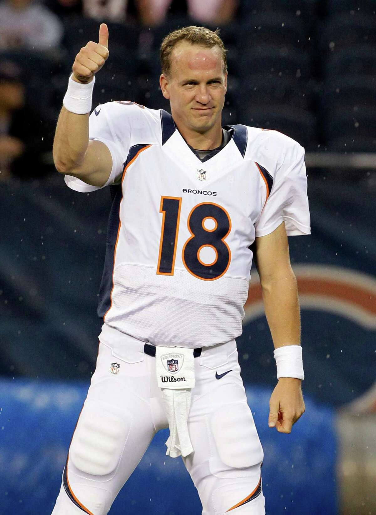 FILE - In this Aug. 9, 2012 file photo, Denver Broncos quarterback Peyton Manning gestures before an NFL preseason football game against the Chicago Bears, in Chicago. A person with knowledge of the results tells The Associated Press that Manning has passed his physical on his surgically repaired neck, clearing the way for him to play in 2014. In what was considered the final formality for his return, Manning passed the exam as required by his contract that will pay him $20 million next season, according to the person who spoke on condition of anonymity because (AP Photo/Nam Y. Huh, File) ORG XMIT: NY163