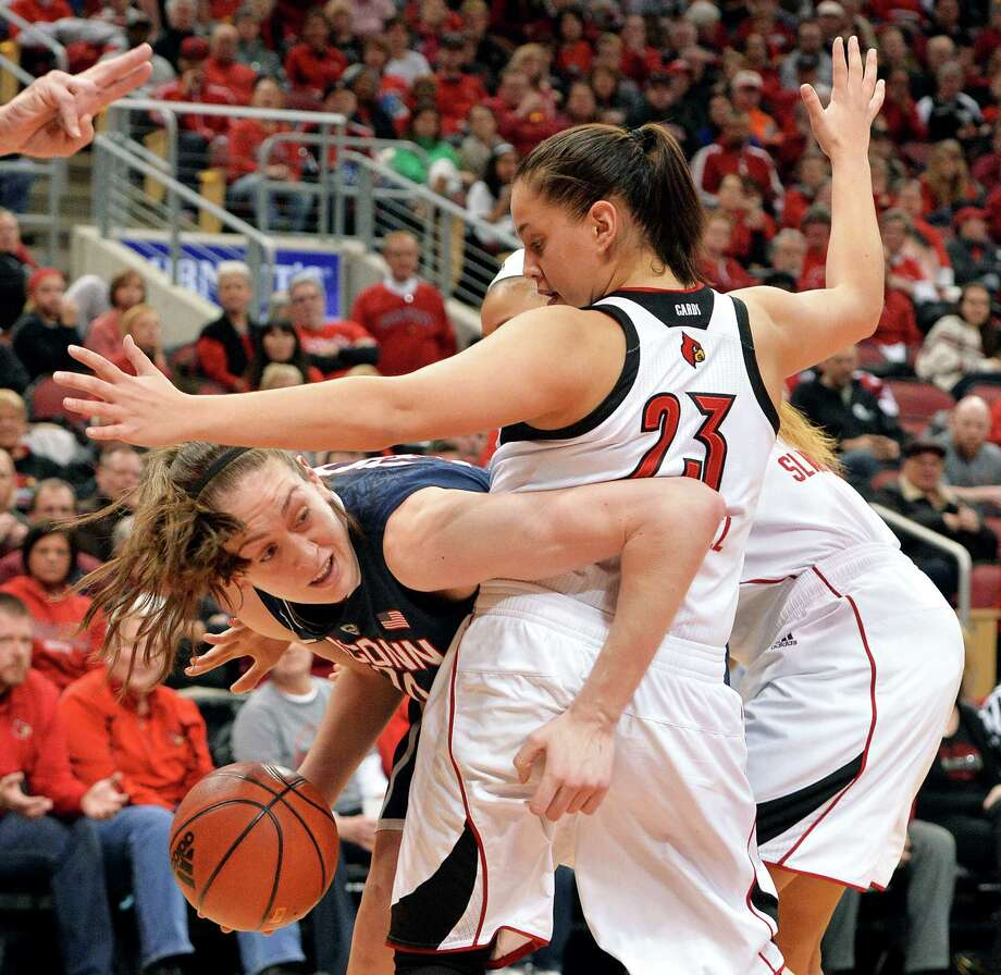 Connecticut's Breanna Stewart, left, attempts to fight her way through the defense of Louisville's Shoni Schimmel, and Antonita Slaughter, rear, during the second half of an NCAA college basketball game, Monday, March 3, 2014, in Louisville, Ky. Connecticut won 68-48. Photo: Timothy D. Easley, AP / Associated Press
