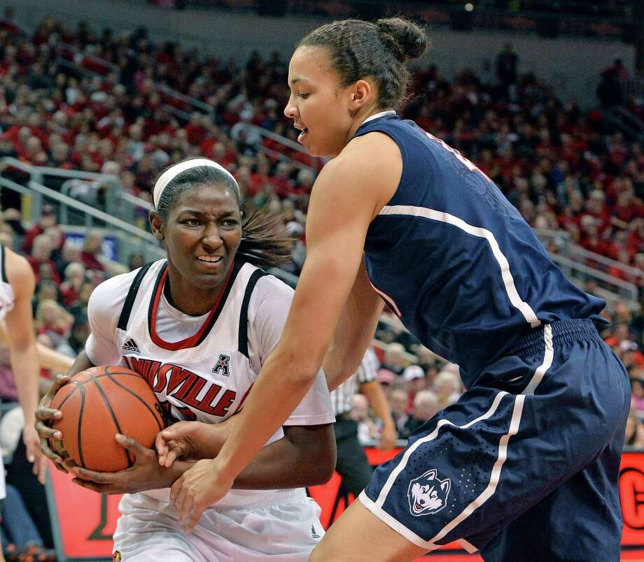 Louisville's Asia Taylor, left, battles Connecticut's Kiah Stokes for a loose ball during the second half of an NCAA college basketball game, Monday, March 3, 2014, in Louisville, Ky. Connecticut won 68-48. Photo: Timothy D. Easley, AP / Associated Press