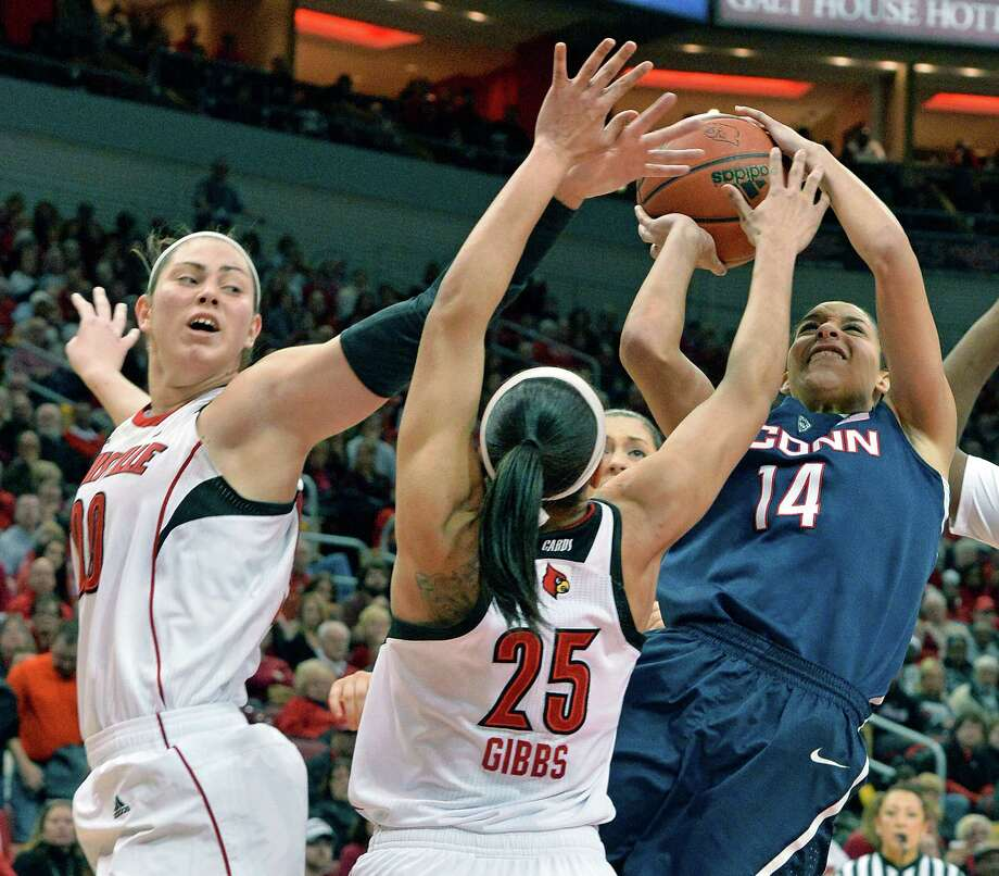 Connecticut's Bria Hartley, right, puts up a shot over the defense of Louisville's Sara Hammond, left, and Tia Gibbs during the second half of an NCAA college basketball game, Monday, March 3, 2014, in Louisville, Ky. Connecticut won 68-48. Photo: Timothy D. Easley, AP / Associated Press