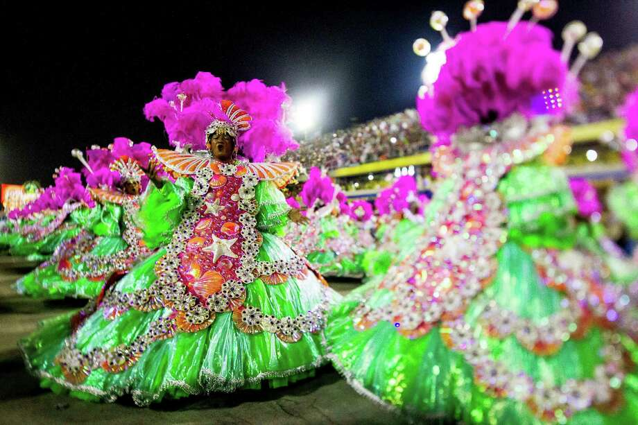 "RIO DE JANEIRO, BRAZIL - MARCH 02: (EDITORS NOTE: A TILT AND SHIFT LENS WAS USED IN THE CREATION OF THIS IMAGE) Members of Mangueira Samba School celebrate during their parade at 2014 Brazilian Carnival at Sapucai Sambadrome on March 02, 2014 in Rio de Janeiro, Brazil. Rio's two nights of Carnival parades begin on March 2 in a burst of fireworks and to the cheers of thousands of tourists and locals who have previously enjoyed street celebrations (known as ""blocos de rua"") all around the city. (Photo by Buda Mendes/Getty Images) ORG XMIT: 476220239 Photo: Buda Mendes / 2014 Getty Images"