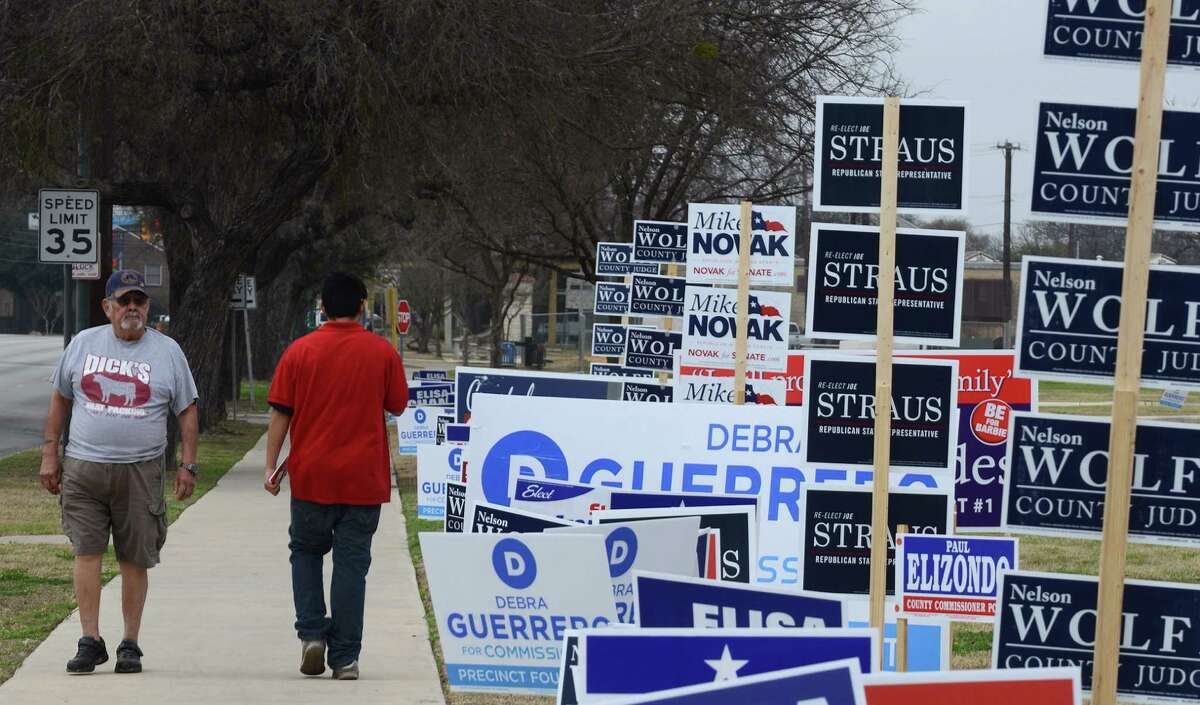 There is a lawn there somewhere amid the campaign signs. Balloting will start in chilly, just-above-freezing weather.