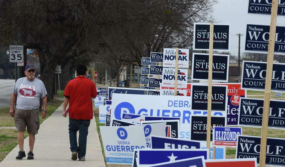 There is a lawn there somewhere amid the campaign signs. Balloting will start in chilly, just-above-freezing weather. Photo: Billy Calzada / San Antonio Express-News / San Antonio Express-News