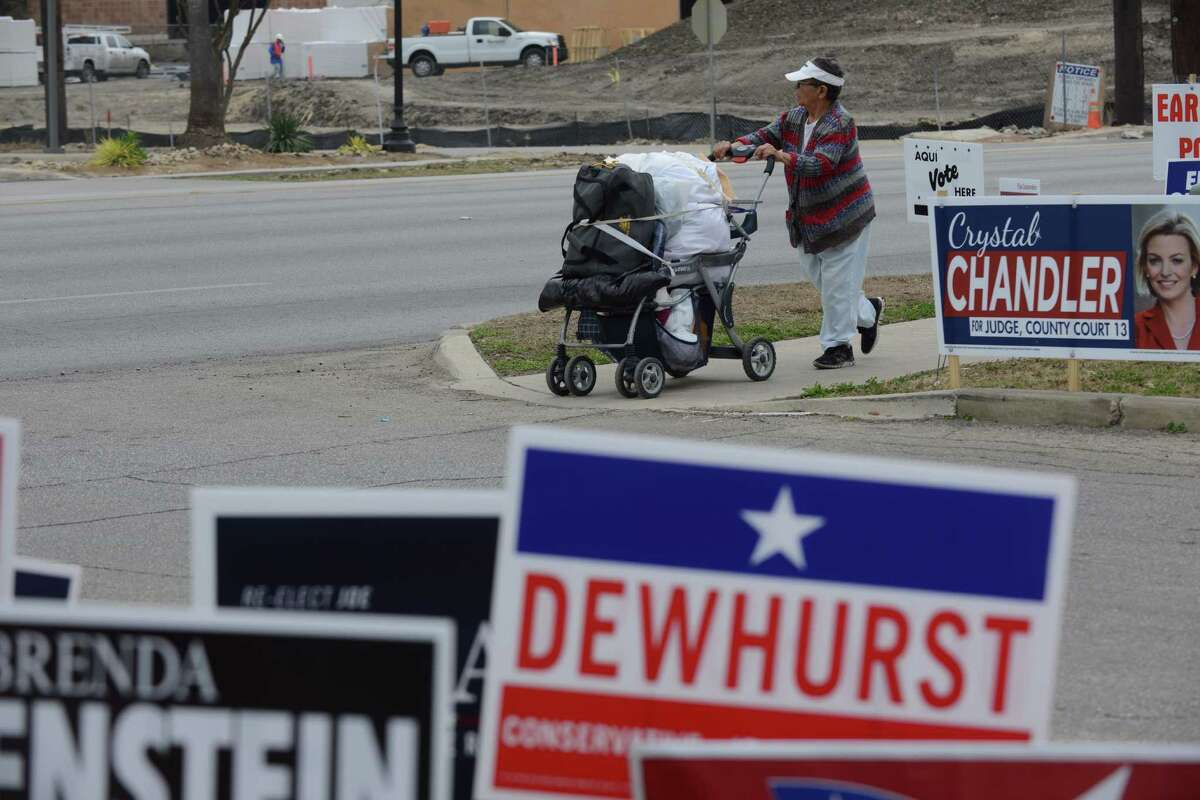 A person pushes a cart on the sidewalk by Lions Field where early voting has started on Tuesday, Feb. 18, 2014.