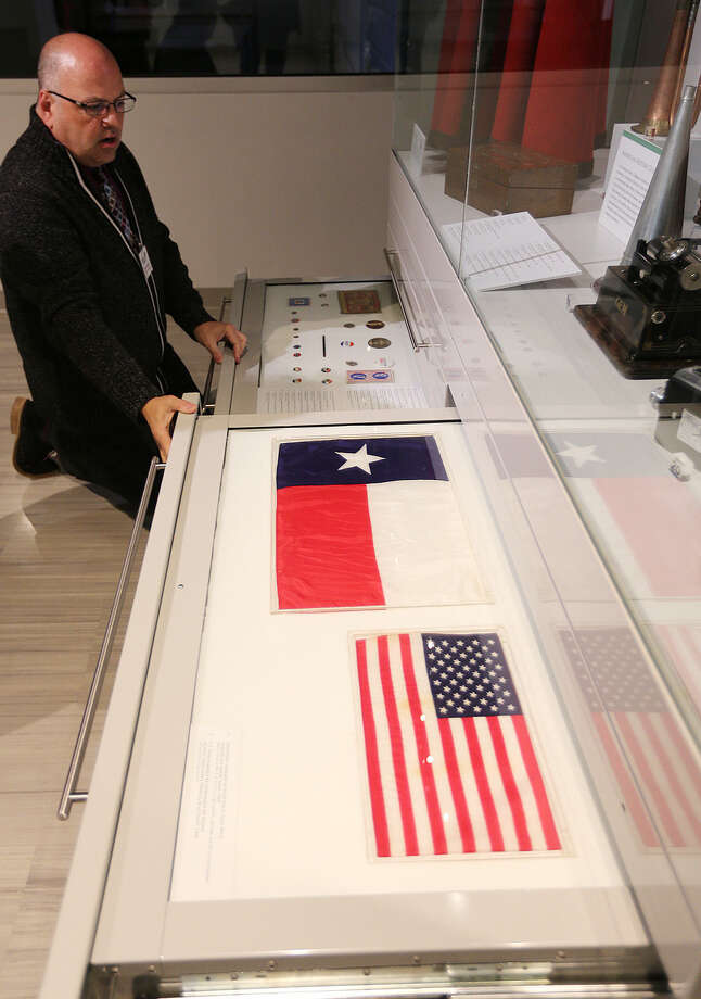Vice Presi-dent of Exhibitions Randall Webster pulls out drawers that help display artifacts in the B. Naylor Morton Research and Collections Center, including a Texas flag carried by Alan Bean during his 1969 moonwalk and the U.S. flag carried by Ed White during the first American space walk in 1965. Photo: Jerry Lara / San Antonio Express-News / © 2014 San Antonio Express-News