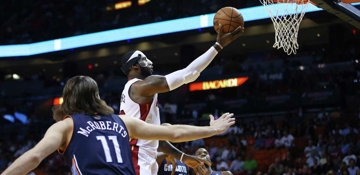 Miami Heat's LeBron James, center, slides through Charlotte Bobcats players Michael Kidd-Gilchrist (14), Josh McRoberts (11) and Al Jefferson (25) for two points during the first half of an NBA basketball game in Miami, Monday, March 3, 2014. (AP Photo/J Pat Carter) ORG XMIT: FLJC101