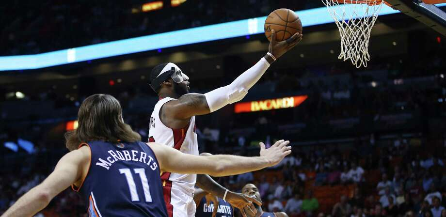 Miami Heat's LeBron James, center,  slides through Charlotte Bobcats players Michael Kidd-Gilchrist (14), Josh McRoberts (11) and Al Jefferson (25) for two points during the first half of an NBA basketball game in Miami, Monday, March 3, 2014. (AP Photo/J Pat Carter) ORG XMIT: FLJC101 Photo: J Pat Carter / AP