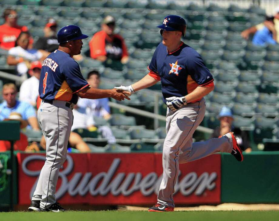 Marc Krauss, right, accepts congratulations from third-base coach Pat Listach on Monday after hitting the Astros' first - and so far, only - home run in four Grapefruit League Games. Krauss' first-inning blast ignited a 4-0 win over the Marlins at Jupiter, Fla. Photo: Karen Warren, Staff / © 2013 Houston Chronicle