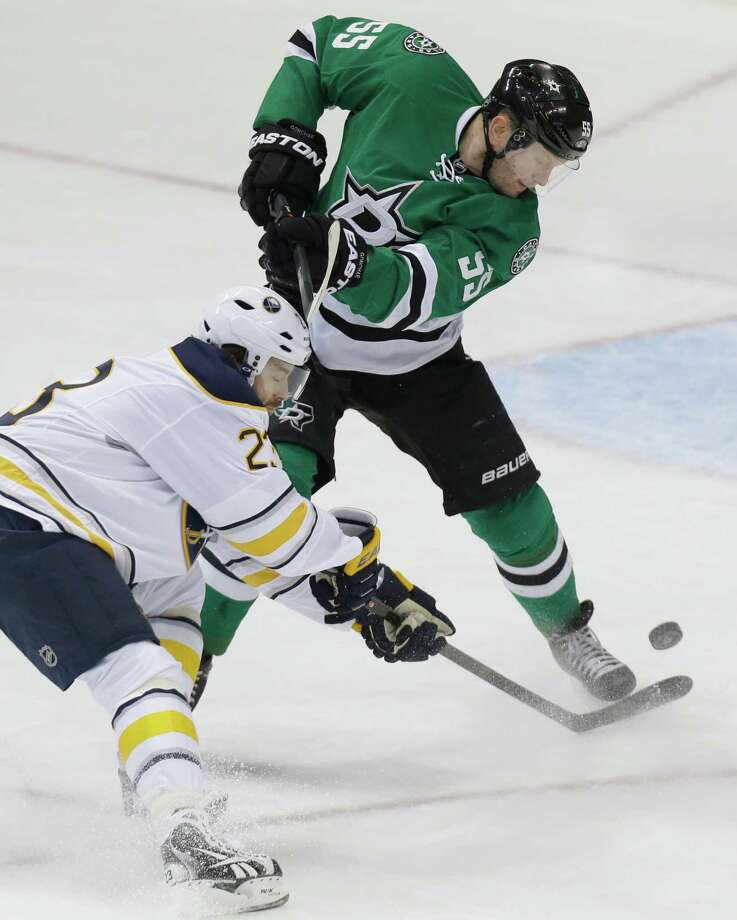 Dallas Stars defenseman Sergei Gonchar (55) and Buffalo Sabres left wing Ville Leino (23) battle for control of the puck during the first period of an NHL hockey game Monday, March 3, 2014, in Dallas. (AP Photo/LM Otero)   ORG XMIT: DNA103 Photo: LM Otero / AP