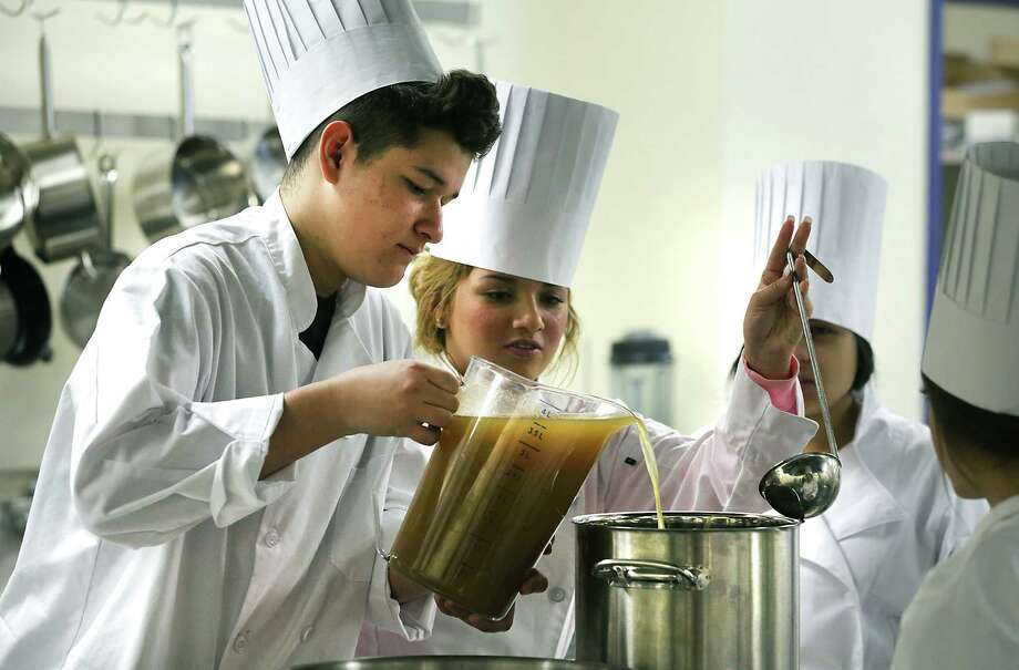 South San High School culinary arts students Austyn Jimenez (left) and Kimberly Tobias (center), dressed for their parts, prepare to make Cajun Shrimp Risotto by mixing in a shrimp broth. Photo: Bob Owen / San Antonio Express-News / © 2012 San Antonio Express-News