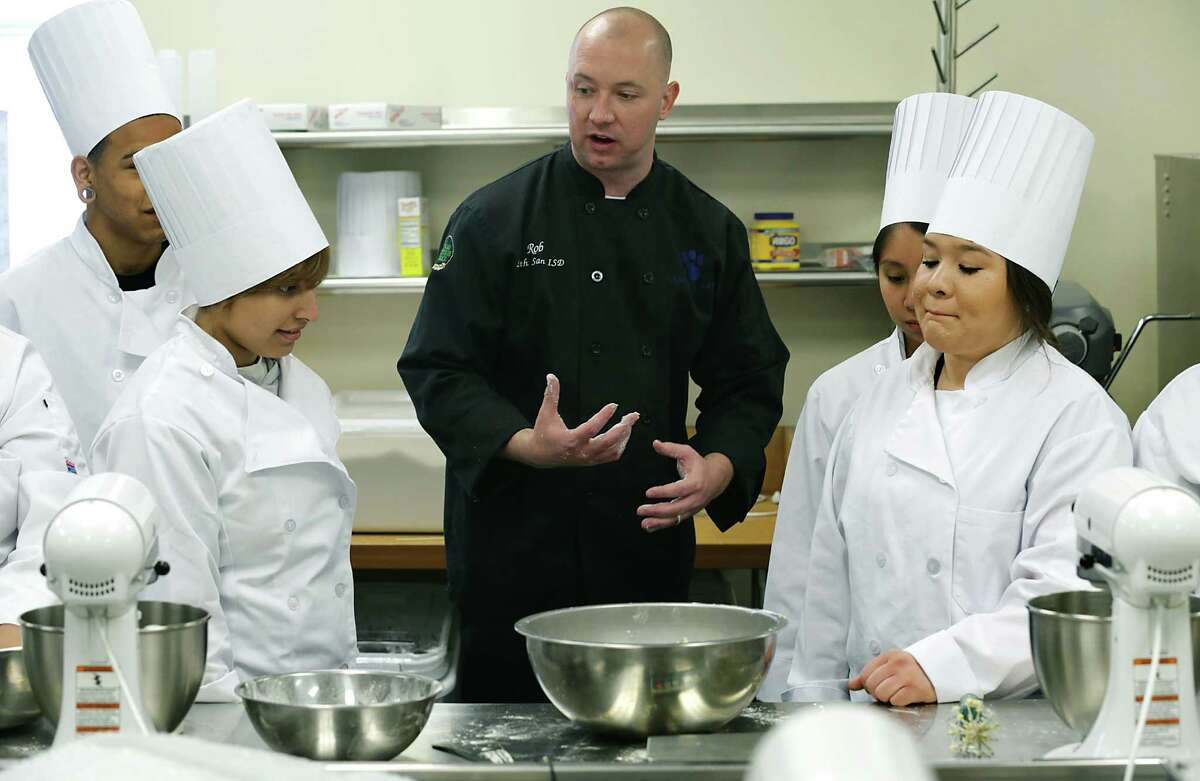 South San High School Culinary Arts Instructor Rob Yoas, center, explains how to mix flour and water and eggs to make pasta dough. At left is Ruth Chavez and at right are Priscilla Gallegos and at far right, Emily Barrera. Monday, March 3, 2014.