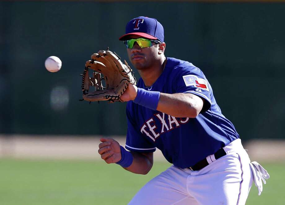 Seahawks QB Russell Wilson, picked by Texas in December's Rule 5 draft, spent a day in Rangers camp Monday but shifts his focus back to football today. Photo: Tony Gutierrez, STF / AP