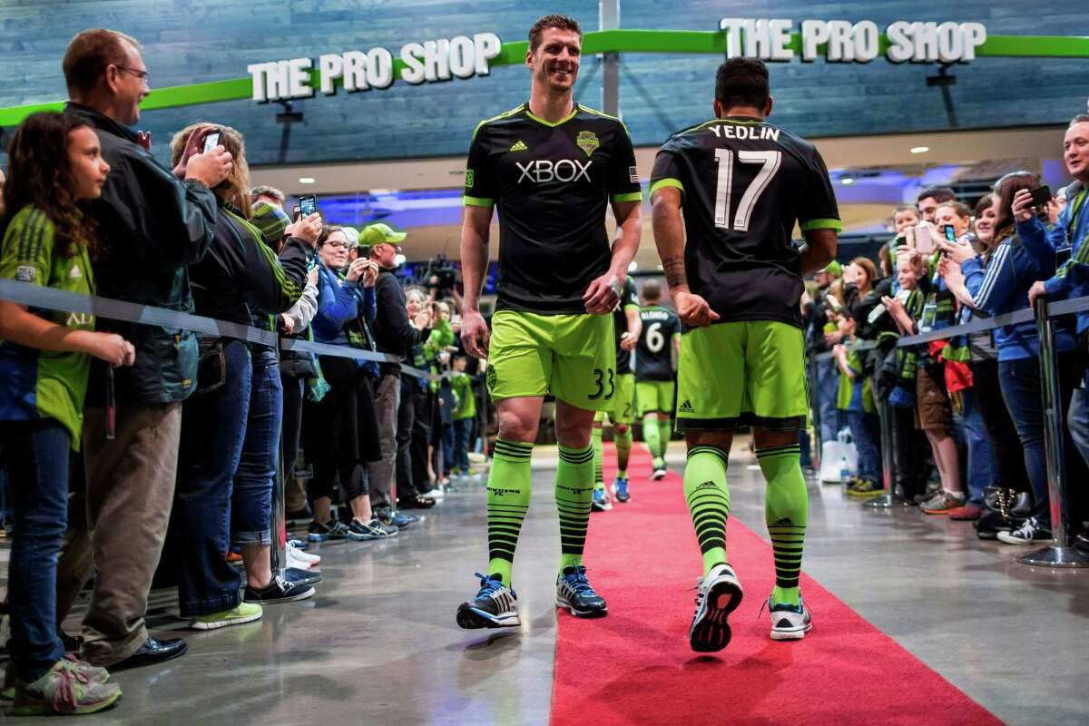 Sounders FC players Kenny Cooper, left, and DeAndre Yedlin, right, show off the new black-and-green third kit uniforms for the 2014 season Monday, March 3, 2014, at CenturyLink Field in Seattle. The season home opener against Sporting KC is Saturday at noon.