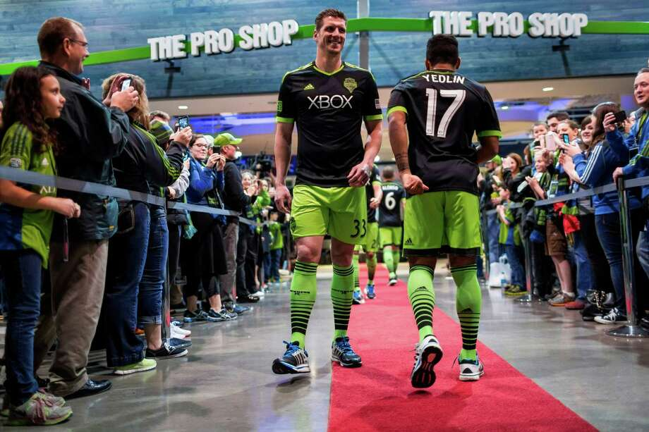 Sounders FC players Kenny Cooper, left, and DeAndre Yedlin, right, show off the new black-and-green third kit uniforms for the 2014 season Monday, March 3, 2014, at CenturyLink Field in Seattle. The season home opener against Sporting KC is Saturday at noon. Photo: JORDAN STEAD, SEATTLEPI.COM / SEATTLEPI.COM