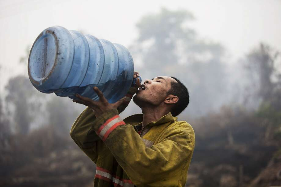 SIAK, RIAU, INDONESIA - MARCH 03:  A firefighter takes a drink after extinguishing a fire burning at a plantation on March 3, 2014 in Siak, Riau, Indonesia. The air quality reached dangerous levels while forest fires continue to burn in Indonesia's Riau province after a long period of dry weather. The smokey haze has reportedly caused more than 25,000 to have respiratory problems.  (Photo by Oscar Siagian/Getty Images) *** BESTPIX *** Photo: Oscar Siagian, Getty Images