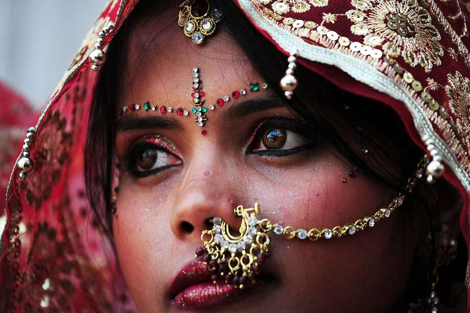 TOPSHOTS An Indian bride looks on as she and ten other women waiting to marry wait for their grooms to arrive at their wedding ceremony at a local Hindu temple in New Delhi on March 3, 2014.  Eleven couples tied the knot at the same time.      AFP PHOTO/Roberto SCHMIDTROBERTO SCHMIDT/AFP/Getty Images Photo: Roberto Schmidt, AFP/Getty Images
