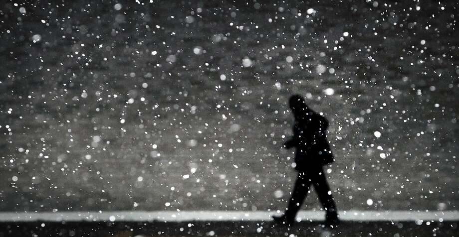 A traveler at the Memphis Airport hustles through the flakes of falling snow to make his flight Monday, March 3, 2014 after a winter storm covered parts of Memphis in a blanket of ice over night. (AP Photo/The Commercial Appeal, Jim Weber) Photo: Jim Weber, Associated Press