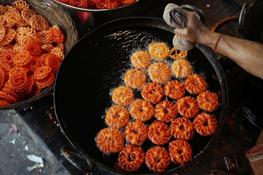 An Indian shopkeeper makes traditional sweets at his shop in Allahabad, India, Monday, March 3, 2014. Allahabad in the northern Uttar Pradesh state is an important Hindu pilgrimage center. (AP Photo/Rajesh Kumar Singh) Photo: Rajesh Kumar Singh, Associated Press