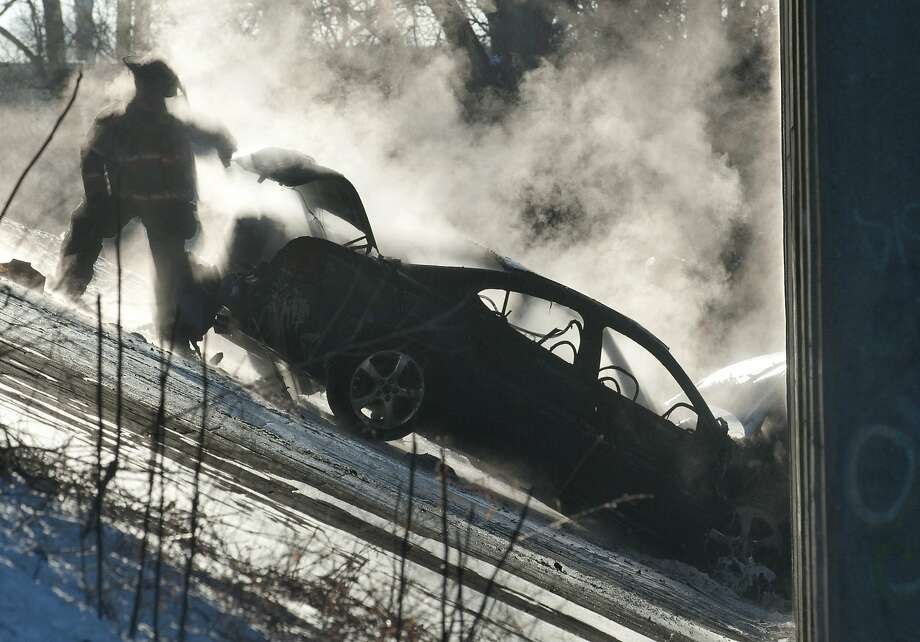 Firefighters at the scene where a car plunged from a U.S. 131 overpass and came to rest along Indian Mill Creek near Ann St. in Grand Rapids, Mich. Monday, March 3, 2014. The driver was killed. (AP Photo/The Grand Rapids Press, Chris Clark) Photo: Chris Clark, Associated Press