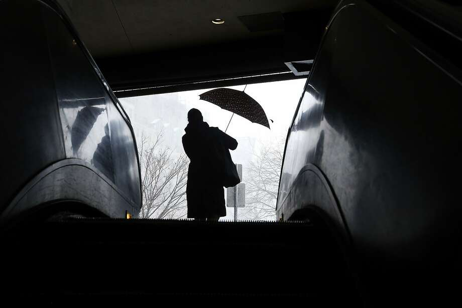 A woman prepares her umbrella before leaving a subway station to head out into the snow in downtown Washington, March 3, 2014.   REUTERS/Jonathan Ernst    (UNITED STATES - Tags: ENVIRONMENT) Photo: Jonathan Ernst, Reuters