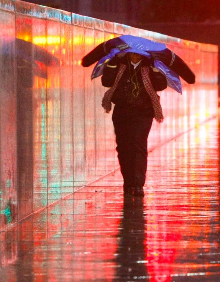 """Sheronda Gilbert shields herself from the weather as she walks along Milam Street. """"It's really cold,"""" she said. (Cody Duty/Houston Chronicle)"""