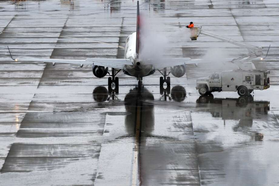 Chemical deicing fluid is sprayed on an aircraft before departure at George Bush Intercontinental Airport on Tuesday, March 4, 2014, in Houston. Winter weather forced cancellation of flights at the airport and dangerous driving conditions for the morning commute. ( Smiley N. Pool / Houston Chronicle ) Photo: Smiley N. Pool, Houston Chronicle
