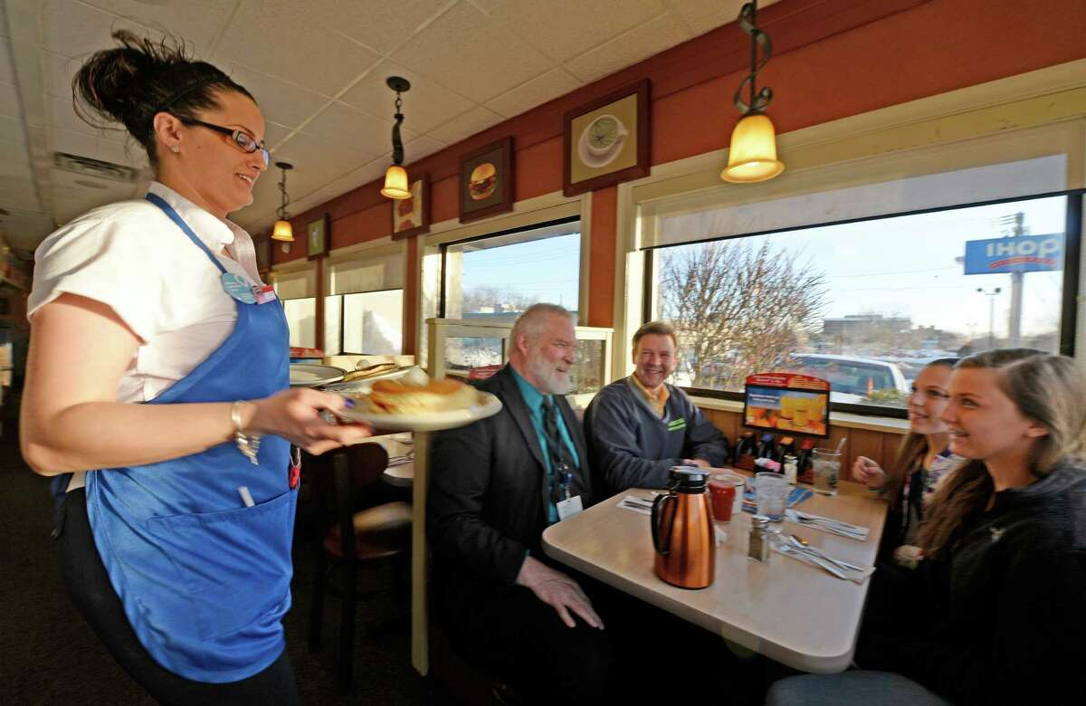 Server Brittany Hull delivers free pancakes to patrons at the IHOP March 4, 2014 in Colonie, N.Y. on National Pancake Day. Patrons enjoying the free pancakes are asked to donate to The Children's Hospital at Albany Medical Center, a Children's Miracle Network Hospital. (Skip Dickstein / Times Union)