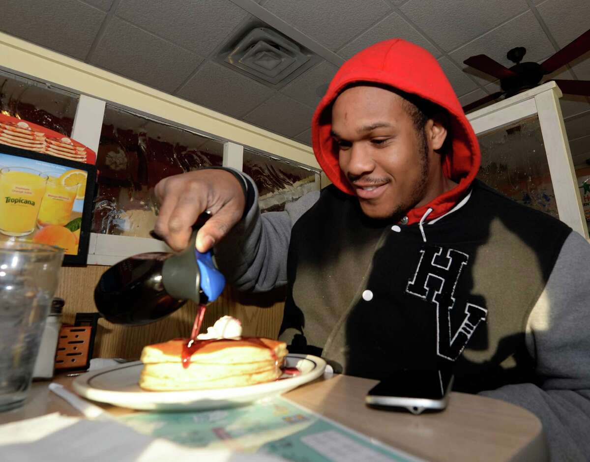 University at Albany student Elijah Dyer spreads syrup on his free pancakes at the IHOP March 4, 2014 in Colonie, N.Y. on National Pancake Day. Patrons enjoying the free pancakes are asked to donate to The Children's Hospital at Albany Medical Center, a Children's Miracle Network Hospital. (Skip Dickstein / Times Union)