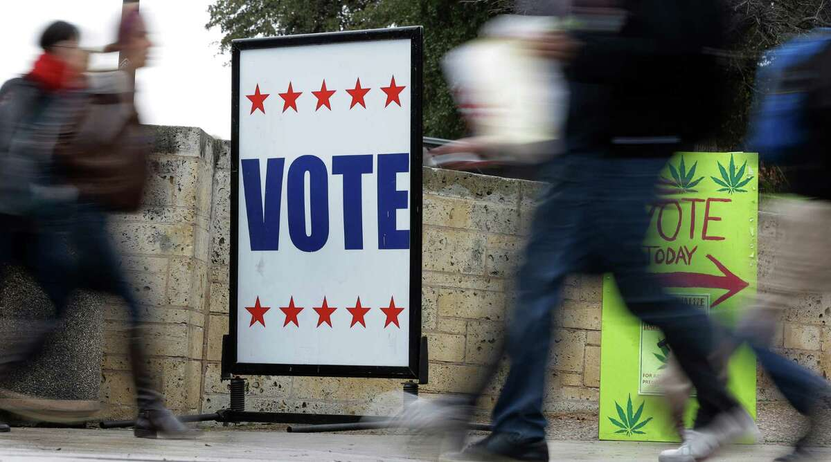 In this Wednesday, Feb. 26, 2014 photo, pedestrians pass voting signs near an early voting polling site, in Austin, Texas.