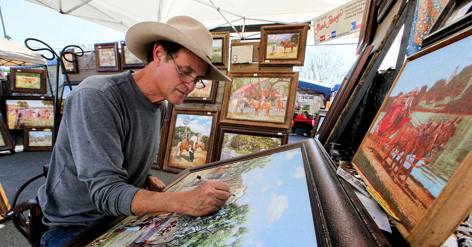 Mark Persyn personalizes one of his prints  for a customer Saturday at The Marketplace at Old Town Helotes. Photo: Photos By Marvin Pfeiffer / Helotes Weekly / Express-News 2014