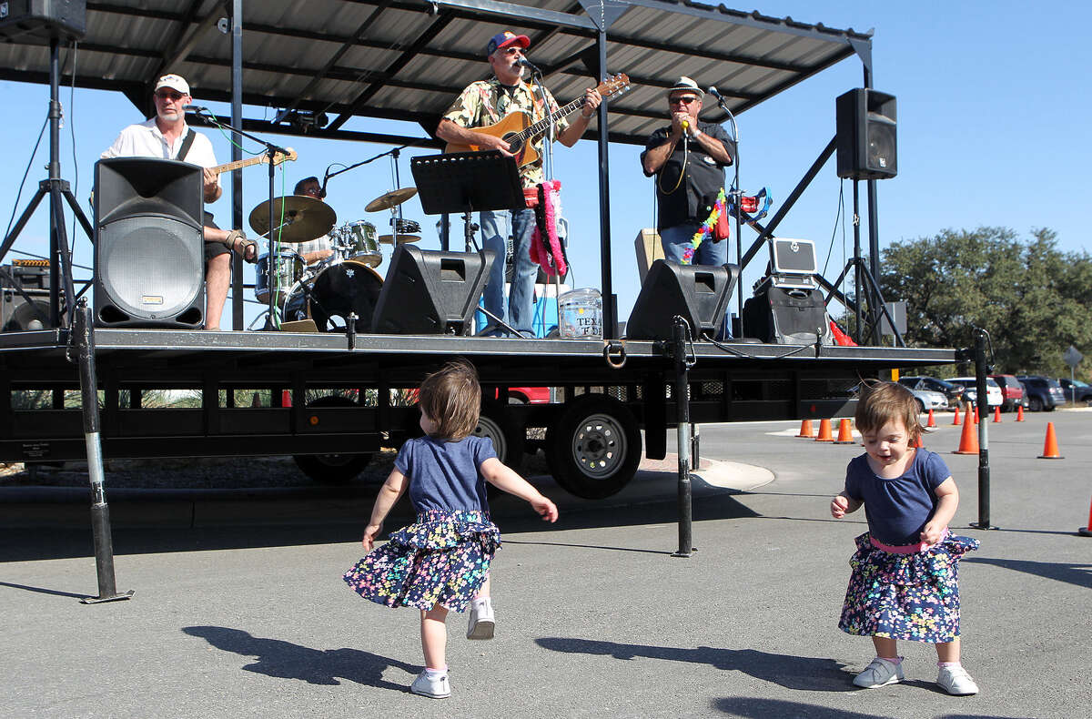 Twins Giana (left) and Olivia Reilly dance to music by the Texas Tide Saturday at Marketplace..