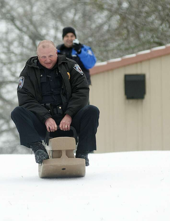 Police investigate sleighing:In Tyler, Texas, Officer Rich Strother commandeers a sled belonging to resident Juan Hernandez and his family (not pictured). Strother and Officer Luis Aparicio made a stop at Woldert Park to spend a few minutes with Hernandez's family, who were enjoying a day off from work and school due to the new snow. Photo: Sarah A. Miller, Associated Press