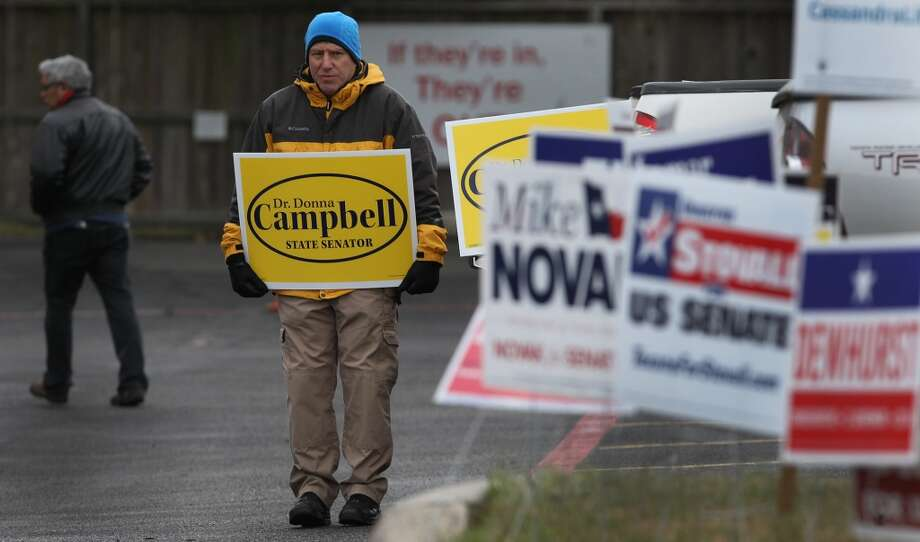 Marcus Booth (center) braves the morning chill Tuesday March 4, 2014 at the Brook Hollow Branch of the San Antonio Public Library on election day. Balloting started in chilly, just-above freezing weather that includes a 20 percent chance of rain. Photo: John Davenport, San Antonio Express-News