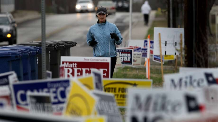 Jeanie Wilkinson (center) braves the morning chill while jogging Tuesday March 4, 2014 by the Brook Hollow Branch of the San Antonio Public Library on election day. Balloting started in chilly, just-above freezing weather that includes a 20 percent chance of rain. Photo: John Davenport, San Antonio Express-News