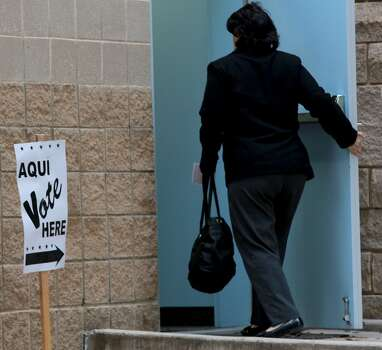 A voter (center) braves the morning chill Tuesday March 4, 2014 at the Brook Hollow Branch of the San Antonio Public Library on election day. Balloting started in chilly, just-above freezing weather that includes a 20 percent chance of rain. Photo: John Davenport, San Antonio Express-News