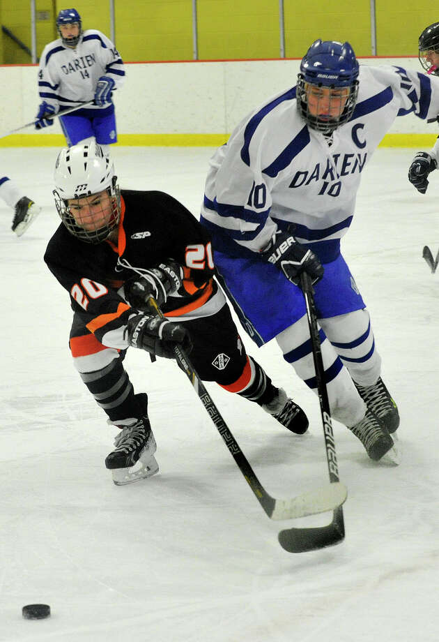 Stamford/Westhill/Staples' Meg Fay and Darien's Ellie Bennett compete for the loose ball during their hockey game at Terry Conners Rink in Stamford, Conn., on Monday, Jan. 13, 2014. Darien won, 7-0. Photo: Jason Rearick / Stamford Advocate
