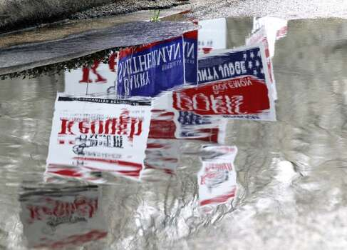 Political signs are reflected in water puddle outside the polling place held at the Friendship Center Community Center, 2235 Lake Robbins Drive,  Tuesday, March 4, 2014 in The Woodlands.  (Melissa Phillip/Houston Chronicle)