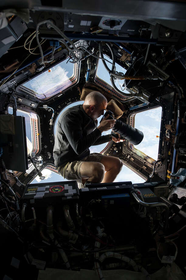 NASA astronaut Chris Cassidy uses a 400-mm lens on a digital camera to snap a photo of something on Earth 250 miles below him. When an astronaut is taking a photo, chances are he or she knows exactly what is being captured, however the sace agency has almost 2 million photos taken by satellite of which it has no identifying information. Now, NASA needs your help telling them what's in their own pictures.  Photo credit: NASA