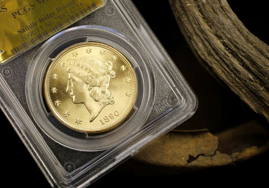 An 1890 double eagle photographed next to the can and stick used to discover the hoard Thursday February 20, 2014 in Tiburon, Calif. A fortune in 19th century gold coins found in the Gold Country of California will soon be for sale on Amazon and to serious collectors by the numismatics experts at Kagin's. Photo: The Chronicle