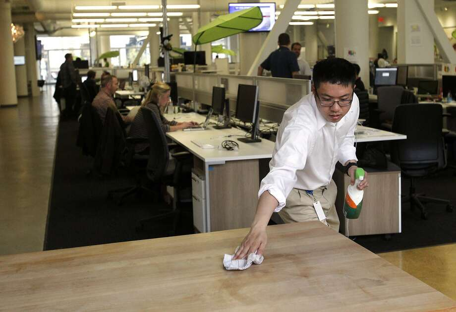 Eric Lin, 26, wipes down a communal table near one of the kitchens Feb. 26, 2014 at Zendesk in downtown San Francisco, Calif. With help from The Arc San Francisco, Lin has been working in Office Services Support since April, 2012. Lin, who works 4 hours a day, five days a week, is in charge of keeping the kitchens and conference rooms stocked and clean. Over the years, he has added hours and new tasks, which he keeps track of using a list with check marks he refers to periodically throughout the day. Lin is able to remember the names of most of the employees he interacts with on a daily basis and even has nicknames for many. He hopes to be re-hired as a Ghiradelli Chocolateer at AT&T Park this spring. Photo: Leah Millis, The Chronicle